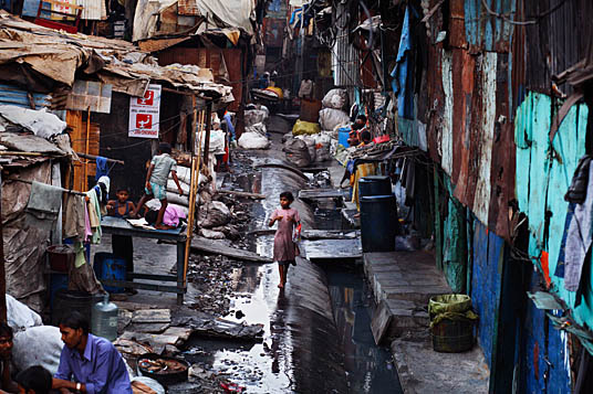 INDIA. Mumbai. 2006.  A girl walks along a water pipe in the Industrial Area of Dharavi. Although it functions as a throroughfare through this area of the slum, the water in the pipes is headed for the more affluent southern areas of the city. Dharavi is one of Mumbai's biggest and longest standing slums. Home to somewhere between 600 000 and one million people, it is a beehive of recycling and manufacturing industries. However, Dharavi sits on prime real estate right in the heart of the booming megapolis, and is in close vicinity to the new Bandra-Kurla Complex, a new financial hub. Dharavi is now scheduled for redevelopment, meaning everything in the slum, for good and bad, is set to be demolished.