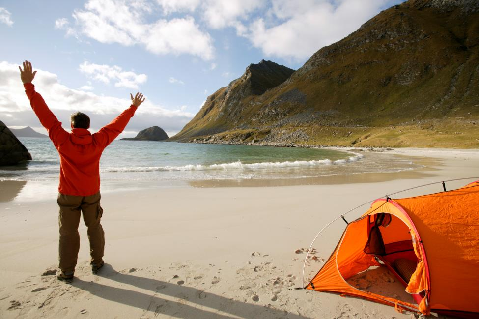 Photo: Nils-Erik Bjørholt / Visitnorway.com A traveler enjoys camping on Hauklandstranda beach in Lofoten. In Norway it's free and legal to pitch a tent almost anywhere on unfenced land.