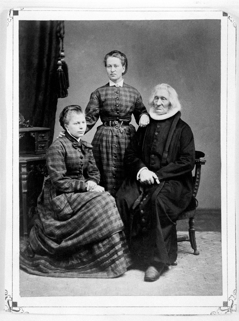Photo: courtesy of Aust-Agder kulturhistoriske senter Left: Theodora Cormontan (standing) with older sister Eivinda and her father, Provst Even Cormontan, c. 1865.