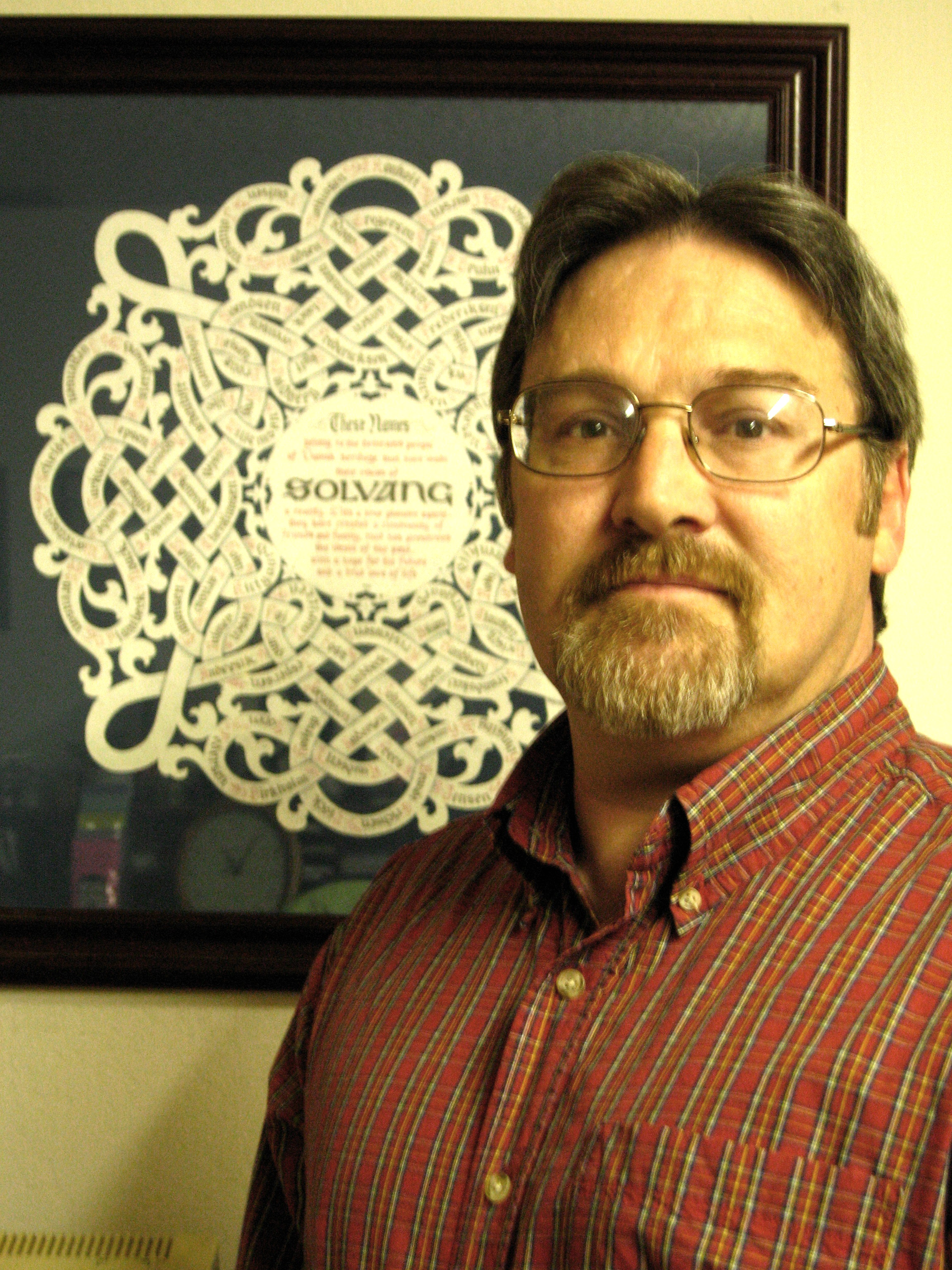 Photo: Larrie Wanberg Rick James Marzullo, Master Papercutter in front of his design honoring the 115 original settlers of Solvang, Calif.