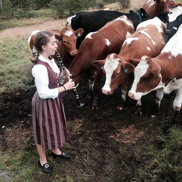 "Photos: Britt Eva Heggheim Dressed as a ""Budeie,"" Jillian serenades the cows at Befring, her cousins' dairy farm."