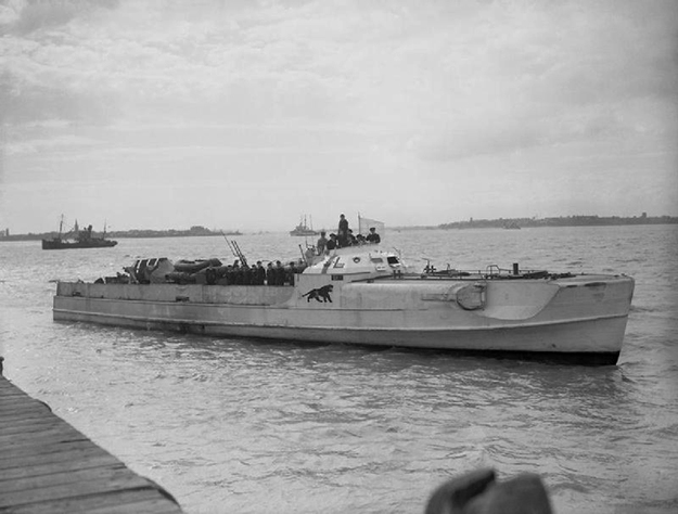"""Photo: Wikimedia Commons The German Schnellboot (""""E-boat"""") S 204 flying a white flag of surrender at the coastal forces base HMS Beehive, Felixstowe, Suffolk (UK), on May 13, 1945."""