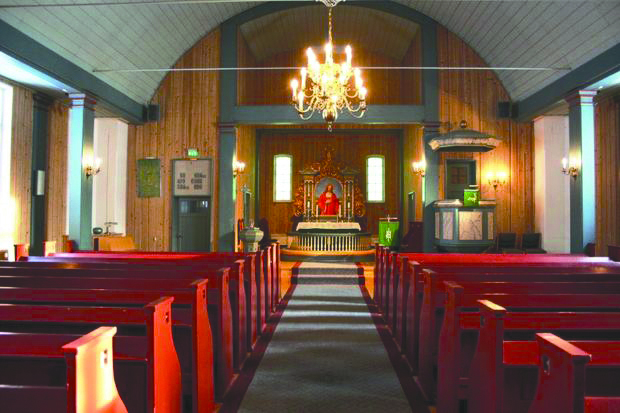 Photo: Kirkesøk.no The interior of Vingrom Kirke, with bright red pews.
