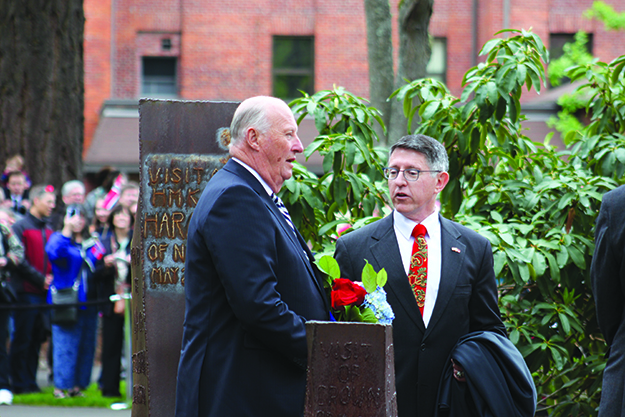 """Photo: Emily C. Skaftun His Majesty King Harald V and Pacific Lutheran University President Thomas W. Krise in front of the """"rune stones"""" commemorating royal visits to PLU, with this most recent inscription fresh on the stone behind the king."""