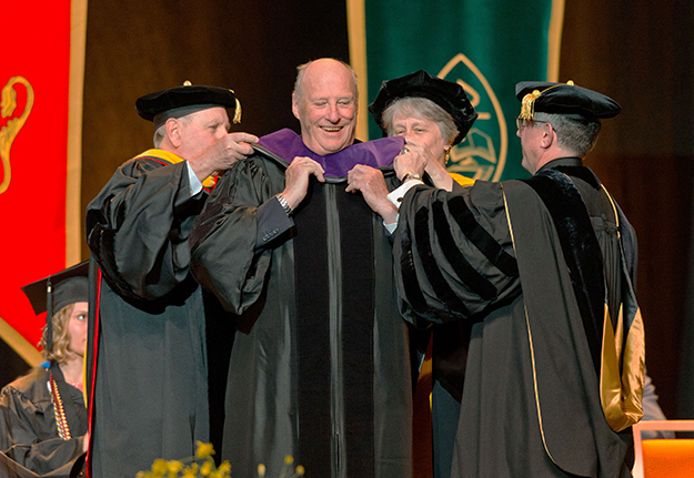 Photo: John Froschauer / PLU Mark Knudson, Professor Jill Whitman, and President Thomas Krise place the hood on HM King Harald V of Norway as he is given Doctor of Laws jure dignitatis during the PLU Commencement in the Tacoma Dome on May 23, 2015.
