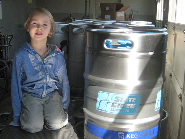 Photo: Barbara K. Rostad Harper Wing, 4, sits by kegs from Slate Creek Brewery which contain Harper Stout, named after her.
