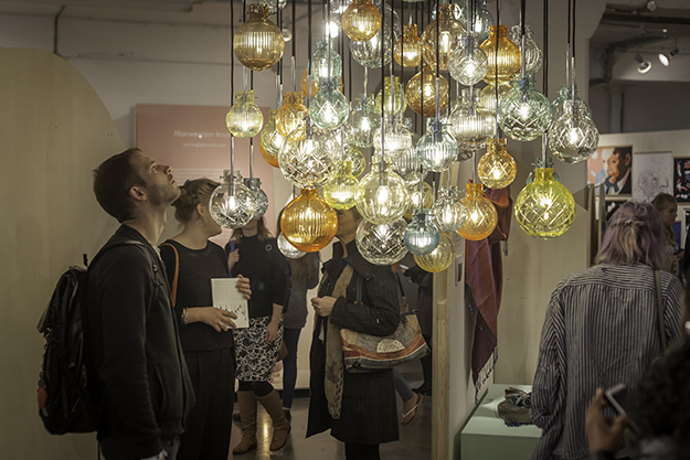 Photo: Dan Weill / 100% Norway  A visitor admires Hadeland Glassverk's Krystallkule lights, glass pendants available in four patterns, many colors, and three sizes. This was just one of many striking exhibits in 100% Norway's tent.