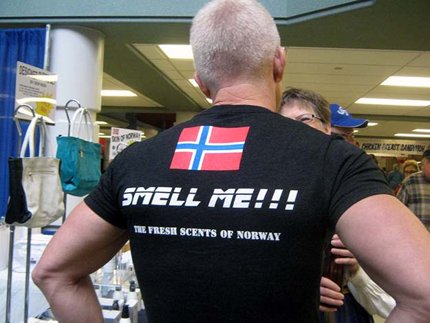 "Photo: Barbara K. Rostad Geir Ness appeals to the sense of smell with two Norwegian perfumes based on ""the fresh scents of Norway."" Ness chats with a customer while wearing his unique t-shirt marketing tool."