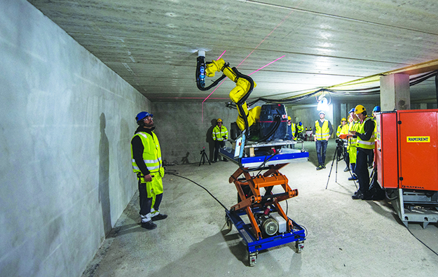 Photo courtesy of nLink Human workers control the robot with an iPad, while it does what used to be brutal physical labor—drilling thousands of precision holes in ceilings for mounting lights and other fixtures.