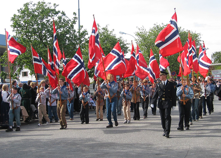 Photo: Ranveig / Wikimedia Commons A group of (human) marchers carry flags at a Syttende Mai parade in Sandnes.