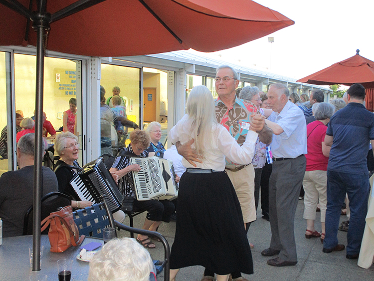Photo: Bill Solum Marit Kristiansen (left) on accordion and her husband Kjell, far right, dancing amid the crowd for Hospitality Night.