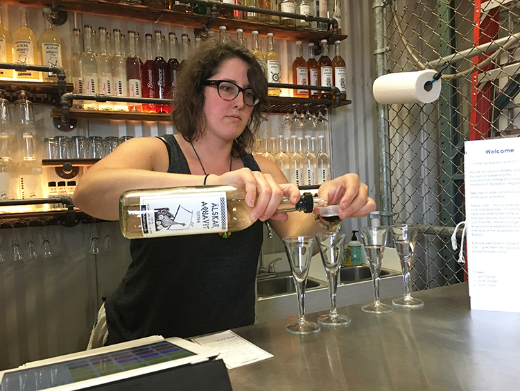 Photo: Emily C. Skaftun Distiller Jane Frazee measures half-ounce tasters of aquavit into snaps glasses for visitors. Despite all the food, Old Ballard is still primarily a distillery and tasting room.