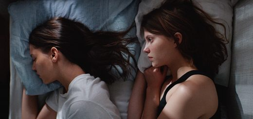 "A scene from ""Thelma"" depicting two young women lying in a bed."