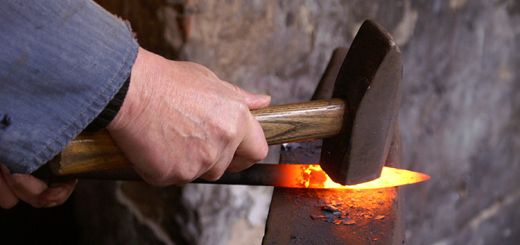 A person forging with a hot form iron.