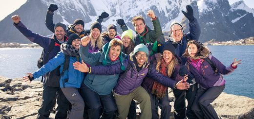 A group of people with Norwegian mountains in the background.