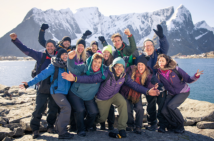 A Group Of People With Norwegian Mountains In The Background