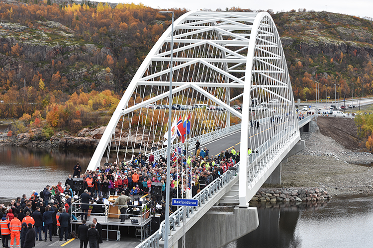 Many people standing on the new bridge.