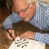 Ed Egerdahl filling in his crossword puzzle.