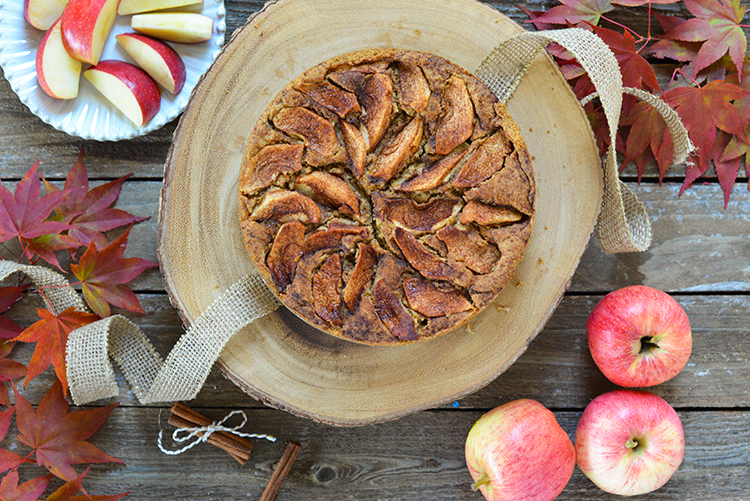 Apple cake with apples and cinnamon on the side.
