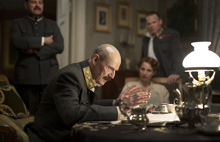 A shot from the film with the king sitting at a desk.
