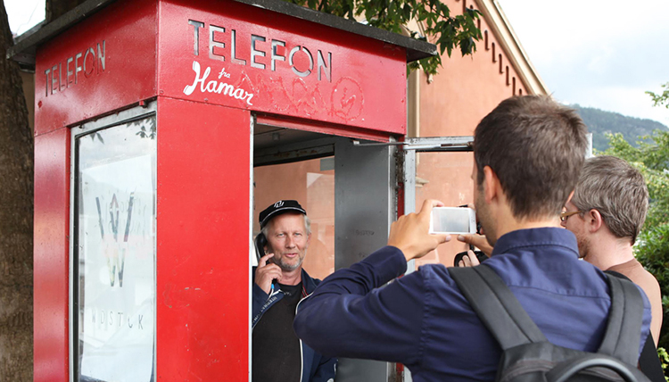 Man answering call in phone booth.