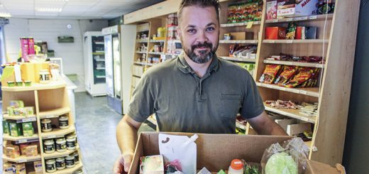 Man holding box of food in vegan store.